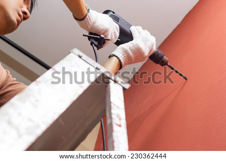 asian handsome man with electric drill on ladder making hole in brown wall / repair, renovation , building and home interior concept - stock photo