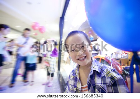 Asian happy boy in shopping mall taking a balloon,china