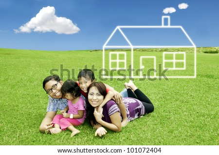 Asian happy family with dream house. Shot in meadow - stock photo