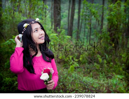 Asian happy woman holding flower while looking up in forest