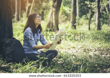 Asian hipster cute teen girl with backpack is reading a map walk in the woods and enjoying sunset.