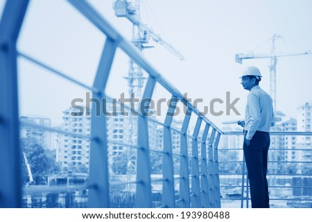 Asian Indian architect visiting construction plant, inspecting the progress. - stock photo