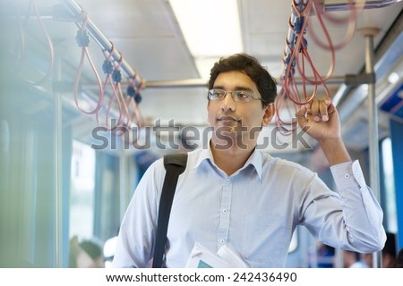 Asian Indian business man taking ride to work, standing inside train. - stock photo