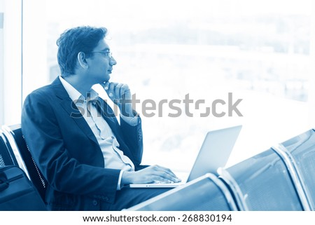 Asian Indian business man waiting his flight at airport, thoughtful and sitting on chair, blue tone. - stock photo