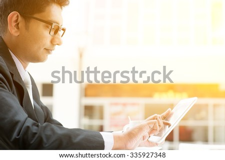 Asian Indian business people using tablet pc at cafe, relaxing with a cup of coffee. India male business man, modern office building with sunlight as background. - stock photo
