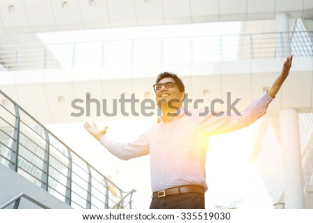 Asian Indian businessman arms outstretched celebrating success, modern office building with morning sunlight as background. - stock photo