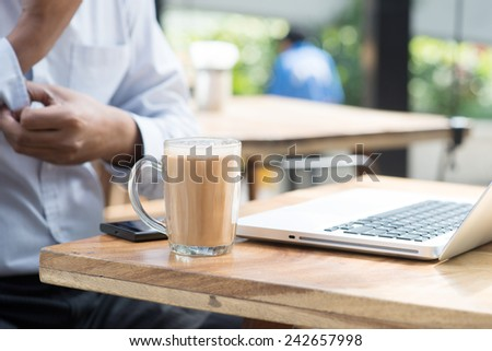 Asian Indian businessman having a cup hot milk tea and rolled up his sleeve during office break. - stock photo