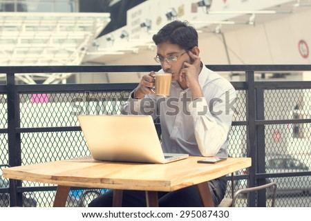 Asian Indian businessman using laptop computer while drinking a cup hot milk tea. - stock photo