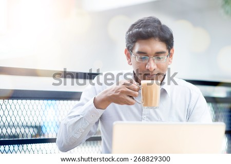 Asian Indian businessman using laptop computer while drinking a cup hot milk tea, outdoor cafe. - stock photo