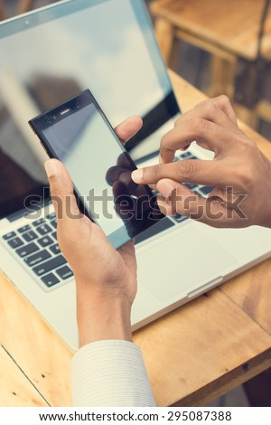 Asian Indian businessman using smartphone and laptop computer at outdoor cafeteria. - stock photo