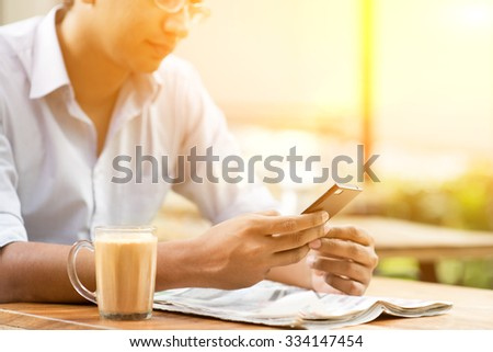 Asian Indian businessman using smartphone at cafeteria, beautiful sunlight background. - stock photo