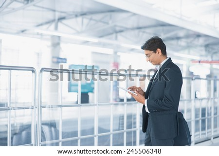 Asian Indian businessman using tablet computer while waiting train at railway station. - stock photo