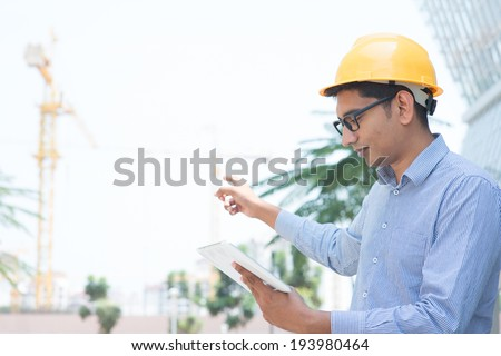 Asian Indian engineer looking at digital computer tablet, pointing to the construction site, inspecting the progress of project. - stock photo