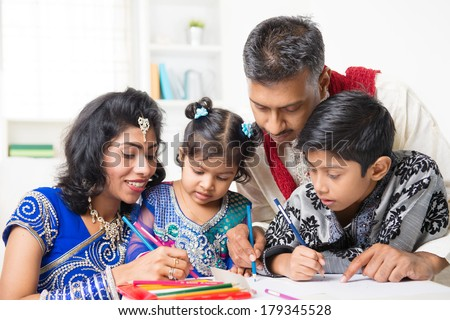 Asian Indian family drawing and painting picture at home. India family lifestyle. Happy parents and children having fun. - stock photo