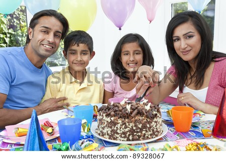 Asian Indian family, mother, father, son & daughter celebrating a birthday party cutting the cake - stock photo