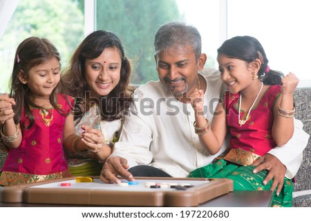 Asian Indian family playing carrom game at home. Parents and children indoor lifestyle. - stock photo