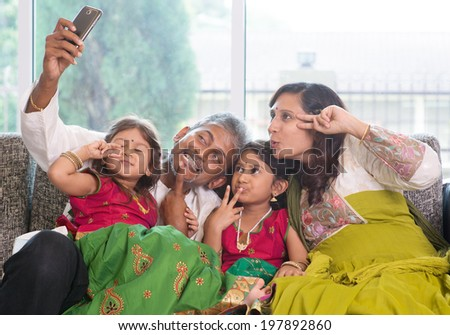 Asian Indian family selfie or self photograph at home. Parents and children indoor lifestyle. - stock photo