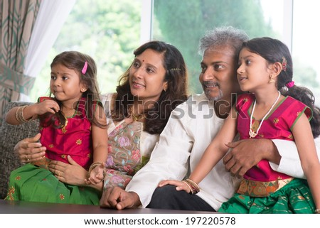 Asian Indian family watching TV. Parents and children indoor lifestyle.