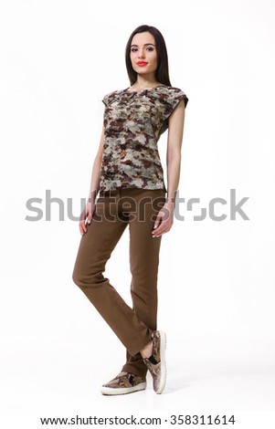 asian indian fashion model in khaki military print sleeveless blouse casual trousers and trainers full body portrait isolated on white - stock photo
