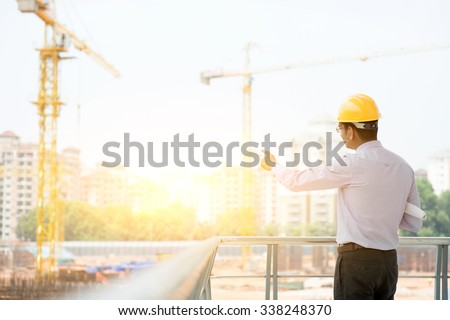 Asian Indian male site contractor engineer with hard hat holding blue print paper pointing at construction site, crane with golden sunlight at the background. - stock photo