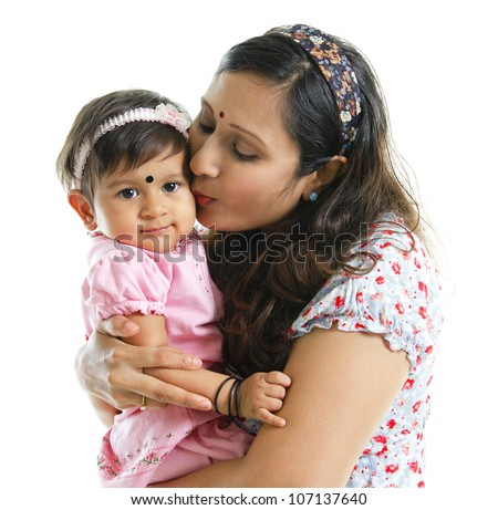 Asian Indian mother kissing her baby girl, isolated on white background