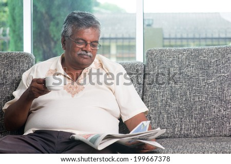 Asian Indian senior adult drinking coffee while reading news paper sitting on sofa at home in morning, elderly retirement indoor living lifestyle. - stock photo