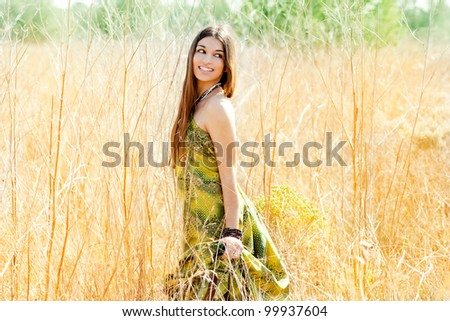 Asian indian woman walking outdoors in golden field with green long dress - stock photo