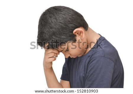 Asian indian 8 year old boy holding his head in shame with isolated white background.
