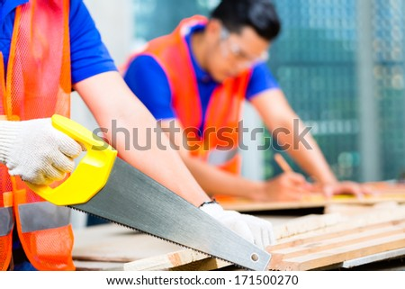 Asian Indonesian builder or craftsman sawing with a saw a wood board of a tower building or construction site wearing protection glasses and gloves - stock photo