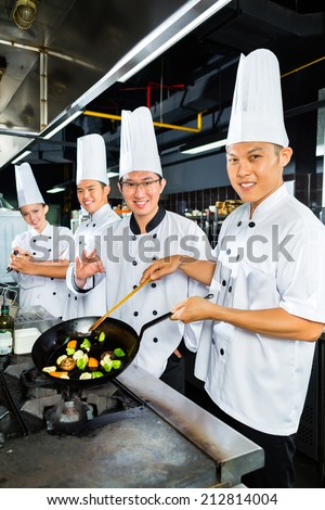 Asian Indonesian chefs along with other cooks in restaurant or hotel kitchen cooking or fry with a pan at the stove - stock photo