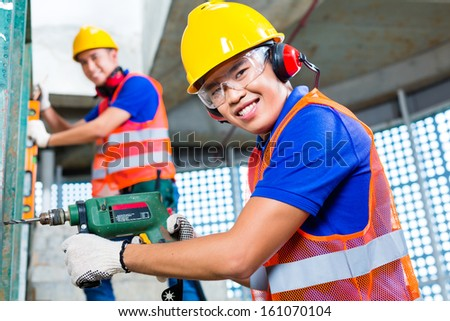 Asian Indonesian construction site workers  drilling with a machine or drill, bubble level, ear protection, gloves and hardhat or helmet in a wall of a tower building  - stock photo