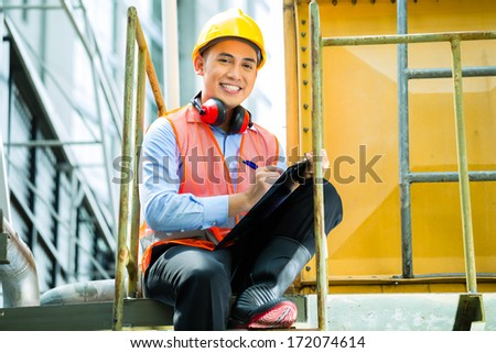 Asian Indonesian construction worker with helmet and safety vest on a building or industrial site in Asia