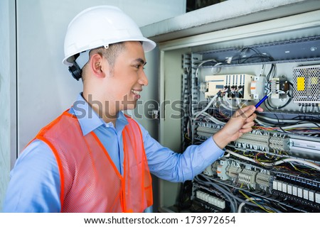 Asian Indonesian Technician or electrician making function test on breaker box or switchbox with power lines on construction site or in factory for acceptance - stock photo