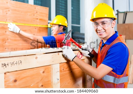 Asian Indonesian worker or craftsman and supervisor closing a delivery or wood box of a tower building or construction site with hammer and nail wearing a hardhat and protection glasses - stock photo