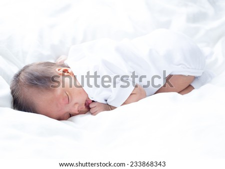 Asian infant baby lying on white bed background