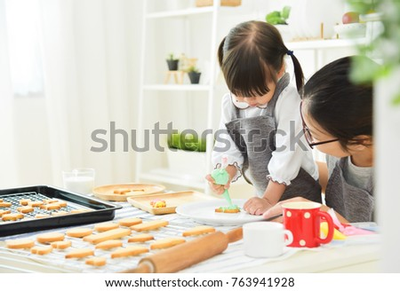 Asian Kid and young mother decorating cookies in the kitchen.