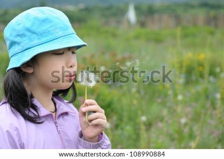 Asian kid blowing dandelions in the field - stock photo