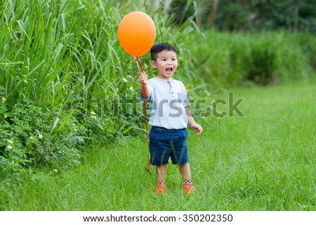 Asian kid catch up with his balloon - stock photo