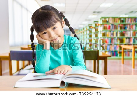 Asian kid enjoy reading in the library.