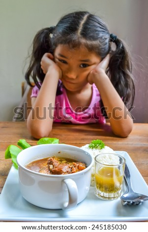 Asian kid getting bored of food - stock photo