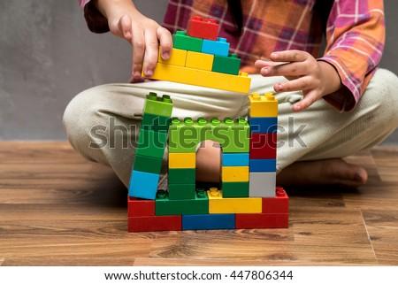Asian kid girl building house from plastic blocks - stock photo