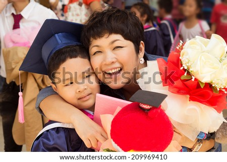 Asian kid in graduation gown and cap. - stock photo
