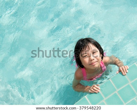 Asian kid in swimming pool on summer vacation