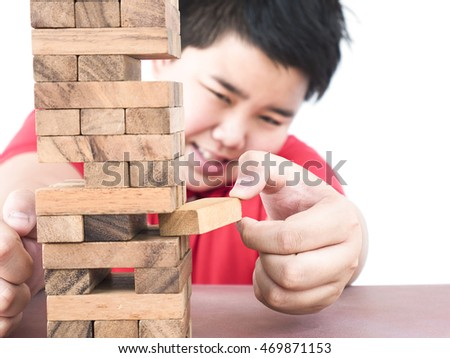 Asian kid is playing a wood blocks tower game for practicing physical and mental skill