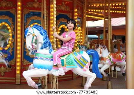 Asian kid playing in Merry go Round - stock photo