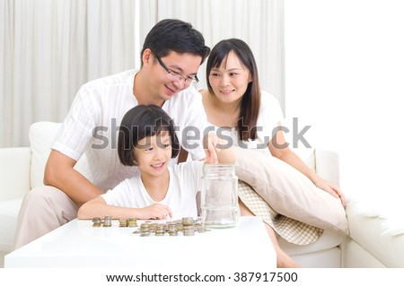 Asian kid putting coins into the glass bottle