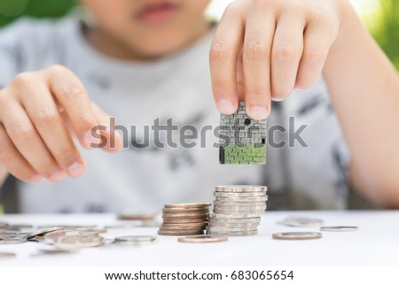 Asian kid's hand putting house model on coins stack. Concept for property ladder, mortgage and real estate investment.