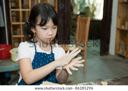Asian kid shaping pottery in the studio - stock photo