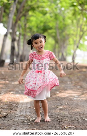 Asian kid show her red dress and dancing in the garden