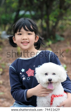Asian kid sitting and holding an toy poodle dog - stock photo